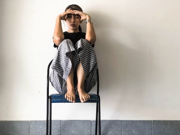 Mujer estresada sentada con una rodilla alta en la silla, con sensación de malestar e infelicidad, síndrome de trastorno depresivo, emoción grave