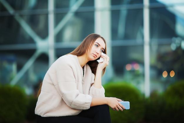 Mujer estresada del trabajo mientras está sentado al aire libre