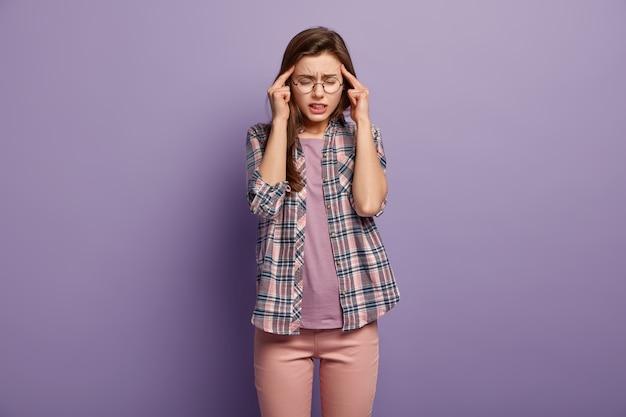 Mujer estresante con exceso de trabajo mantiene los dedos en las sienes, sufre de dolor de cabeza o migraña