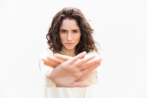 Mujer estricta y seria al hacer que la mano pare el gesto