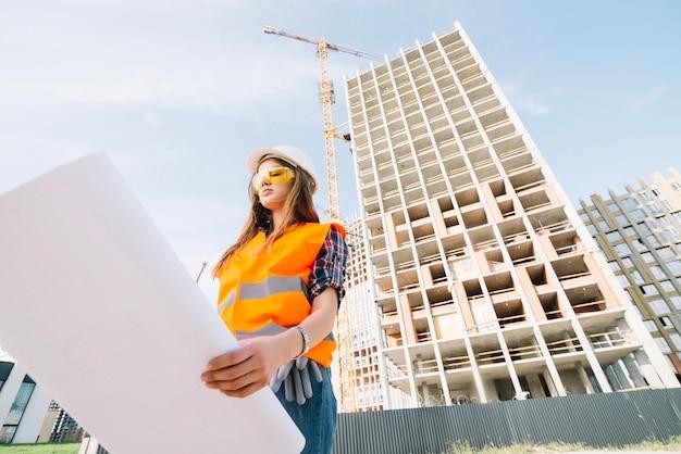 Mujer estudiando borrador en el sitio de construcción