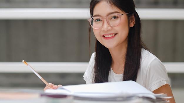 Mujer estudiante asiática leyendo libros en la biblioteca de la universidad