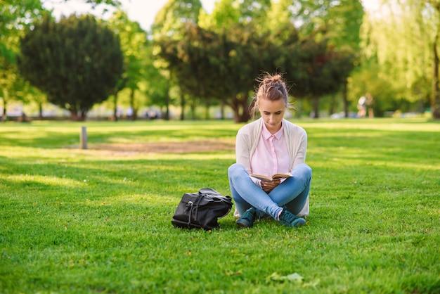 Mujer estudiante está estudiando al aire libre en el campus universitario al atardecer.