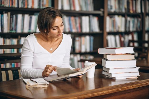 Mujer estudiante estudiando en la biblioteca y tomando café