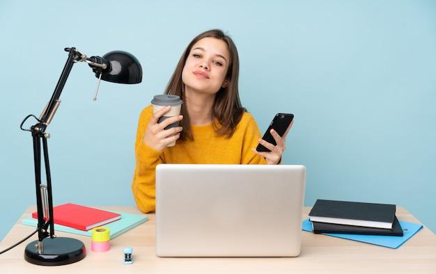 Mujer estudiante estudiando en su casa aislada en la pared azul con café para llevar y un móvil