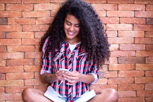 Mujer estudiante feliz con peinado afro sentado con fondo de pared de ladrillo usando teléfono celular y sonriendo.
