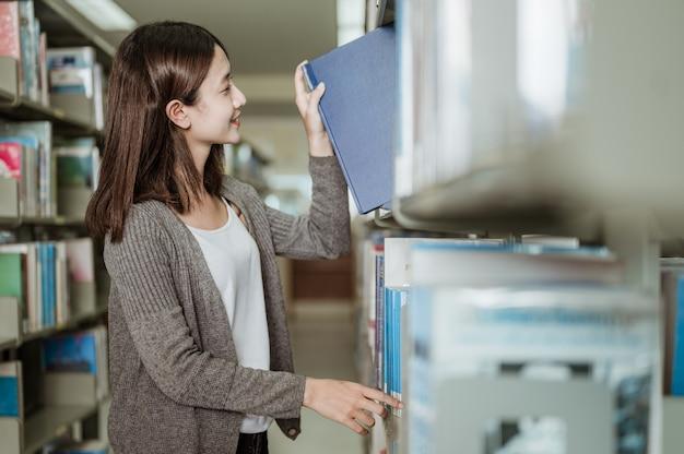 Mujer estudiante feliz tomando el libro del estante en la biblioteca. concepto de educación, escuela, biblioteca y conocimiento.