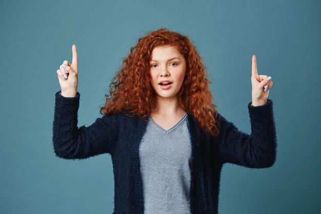 Mujer de estudiante jengibre apuesto relajado con pecas con expresión feliz, apuntando hacia arriba con los dedos en ambas manos sobre fondo azul. copia espacio