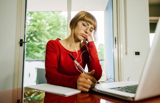 Mujer estudiante molesta estudiando en casa con ordenador portátil. concepto de escuela en línea