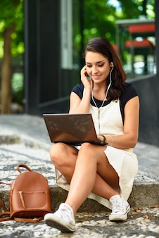 Mujer del estudiante que usa el ordenador portátil que se sienta en pasos urbanos.