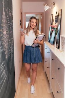 Mujer estudiante sonriente mirando su teléfono móvil mientras camina junto a una pizarra