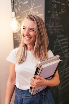 Mujer estudiante sonriente sosteniendo un portátil delante de una pizarra