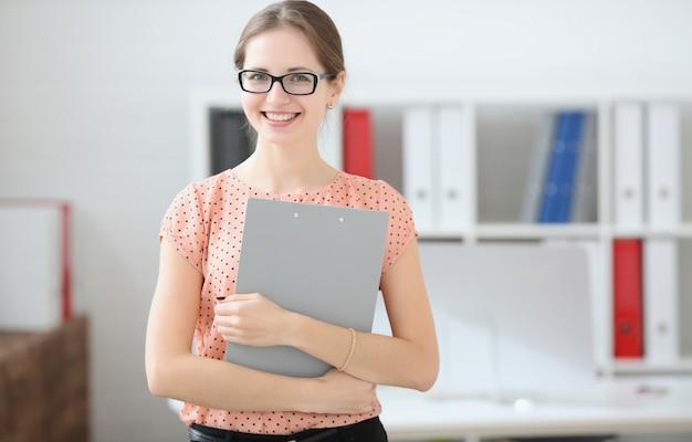 Mujer estudiante sosteniendo una tableta para notas en las manos de la audiencia