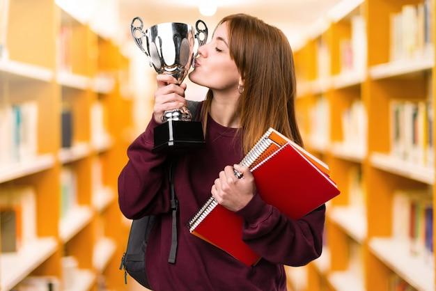 Mujer estudiante sosteniendo un trofeo en el fondo desenfocado. de vuelta a la escuela