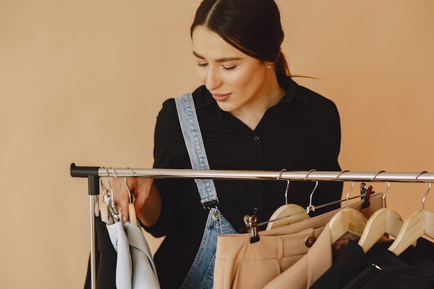 Mujer en un estudio con mucha ropa