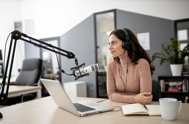 Mujer en un estudio de radio con micrófono y café