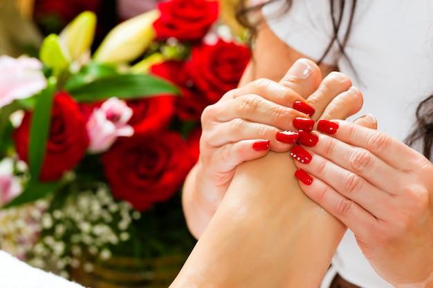 Mujer en estudio de uñas recibiendo masaje de pies