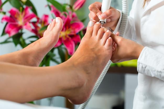 Mujer en estudio de uñas recibiendo pedicura