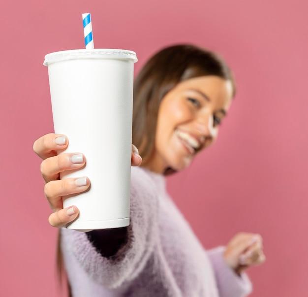 Mujer en estudio sosteniendo un jugo