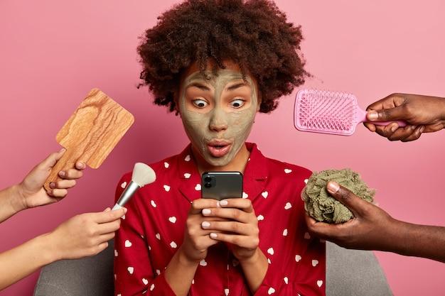 Mujer estupefacta mira con sorpresa el teléfono móvil, viste ropa doméstica informal
