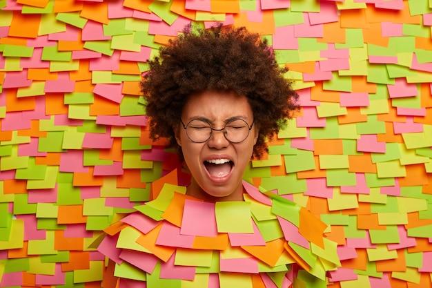 Mujer étnica afligida y afligida llora de desesperación, mantiene la boca bien abierta, sufre a causa de una crisis nerviosa, lloriquea fuerte, grita y se queja sobre algo, posa a través de la pared de papel, tiene pegatinas