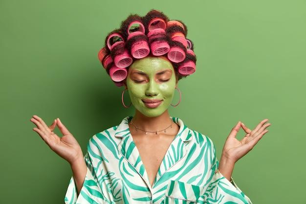 Mujer étnica aliviada usa máscara facial de belleza, se para con los ojos cerrados, medita en casa mientras se somete a tratamientos de spa, entrena yoga, hace un peinado perfecto, se relaja en un ambiente doméstico.