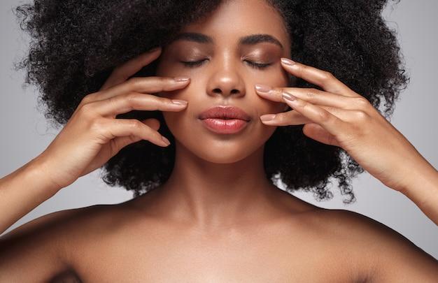 Mujer étnica aplicar crema en la cara