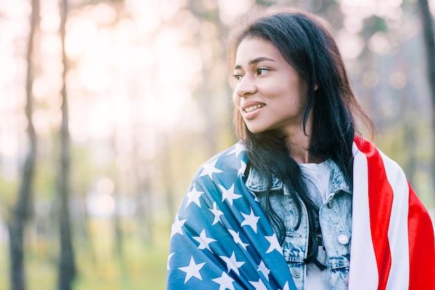 Mujer étnica atractiva posando con la bandera de estados unidos.