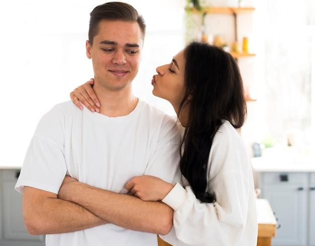 Mujer étnica va a besar en mejilla novio