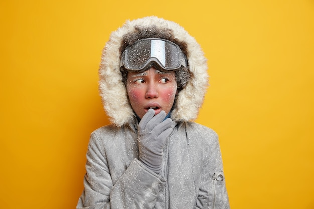 Mujer étnica desconcertada con el rostro cubierto por el hielo siente frío mira hacia otro lado lleva chaqueta de invierno guantes se congela durante el clima helado.
