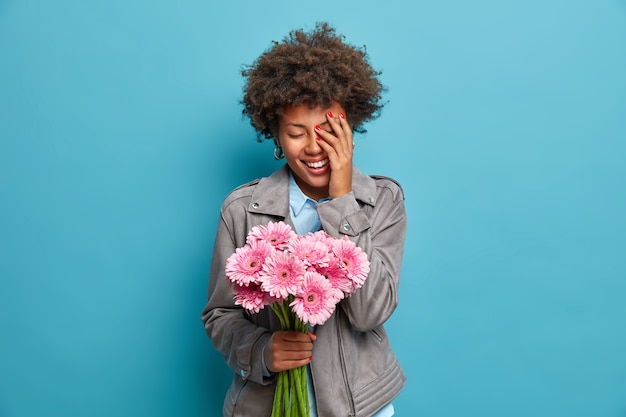 Mujer étnica llena de alegría hace cara de palma, sostiene un ramo de flores de margarita gerbera