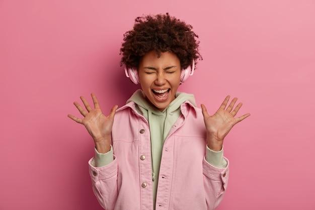 Mujer étnica llena de alegría levanta las palmas, exclama positivamente