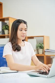Mujer étnica moderna que trabaja con la computadora portátil en la oficina