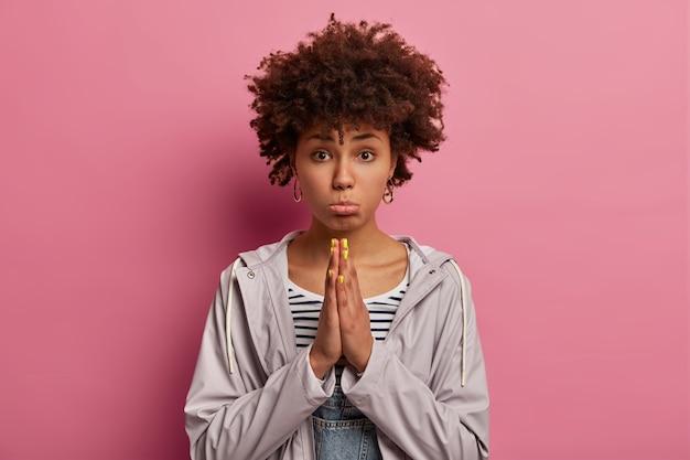 Mujer étnica nerviosa y abatida con cabello rizado, tiene una mueca de mendicidad molesta, hace un gesto de oración, suplica un favor, frunce los labios, usa un anorak informal, posa sobre una pared rosa, suplica con esperanza