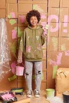 La mujer étnica positiva hace la renovación en el hogar sostiene un cubo con pintura y el pincel tiene una expresión feliz ya que el trabajo casi terminado restaura las paredes del nuevo apartamento vestido con ropa sucia informal