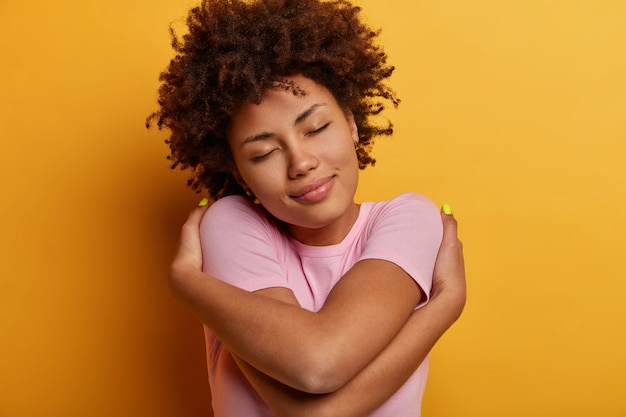 Mujer étnica rizada tranquila complacida se siente bien, se abraza a sí misma