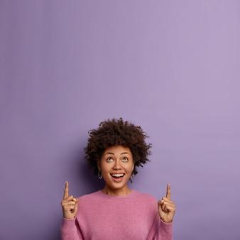 Mujer étnica sonriente alegre apunta arriba, anuncia objeto fresco
