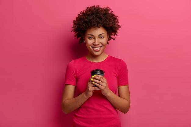 Mujer étnica sonriente de aspecto agradable disfruta de café recién hecho