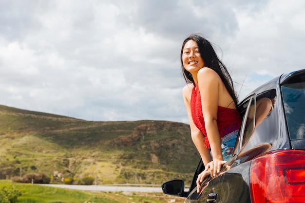 Mujer étnica sonriente mirando por la ventana del coche