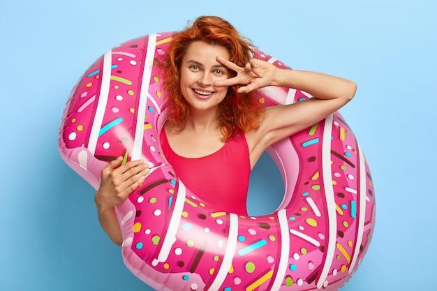La mujer europea alegre y complacida posa con el anillo de natación inflable, viste un bikini rojo de moda