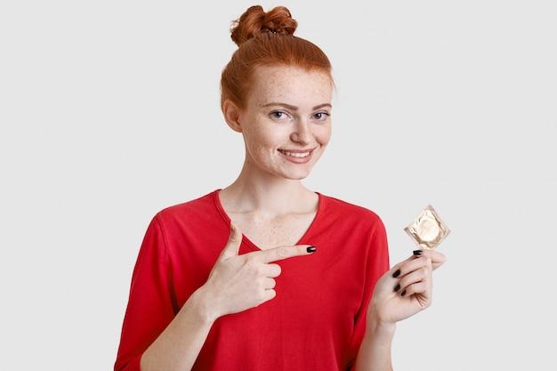 Mujer europea astuta positiva con piel pecosa, señala el condón, se impide a sí misma como protagonista de la vida sexual, usa ropa roja, aislada sobre la pared blanca. concepto de personas, embarazo y seguridad