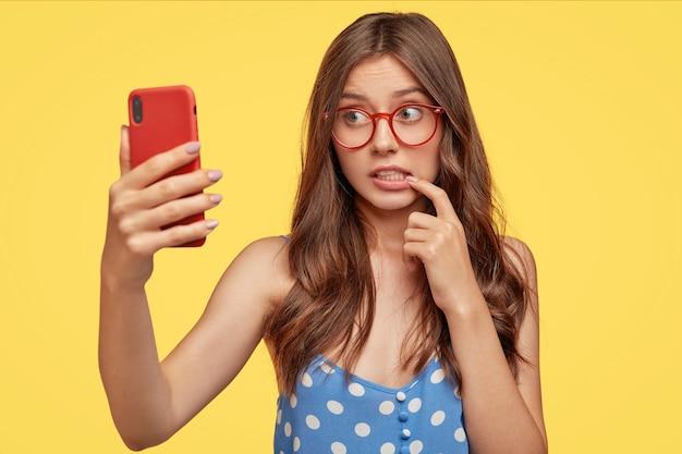 Mujer europea desconcertada muerde el dedo índice, hace retrato selfie de dispositivo electrónico