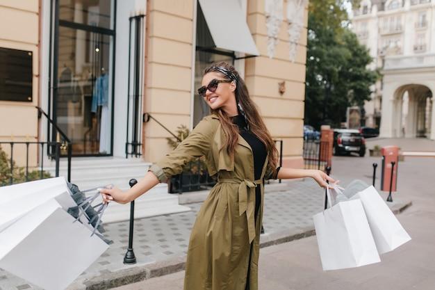 Mujer europea despreocupada con pelo largo disfrutando de fin de semana y agitando bolsas de la tienda con una sonrisa