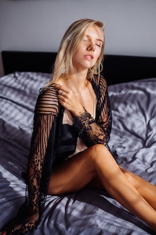 Mujer europea en forma sexy en el dormitorio a la luz del amanecer en cuerpo beige y capa de encaje transparente negro