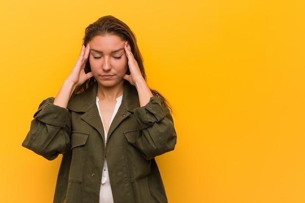 Mujer europea joven aislada sobre el amarillo que toca sus templos y que tiene dolor de cabeza.
