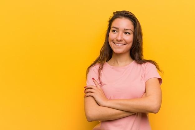 Mujer europea joven aislada sobre el fondo amarillo que sonríe confiado con los brazos cruzados.