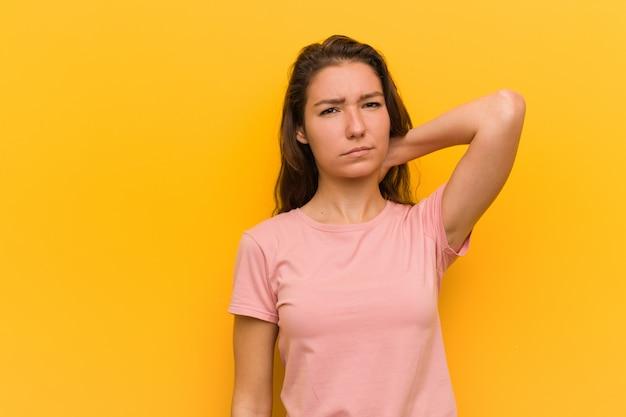 Mujer europea joven aislada sobre la pared amarilla que sufre dolor de cuello debido al estilo de vida sedentario.