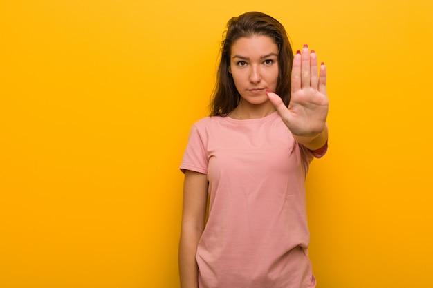 Mujer europea joven aislada sobre la situación amarilla con la mano extendida que muestra la muestra de la parada, previniéndole.