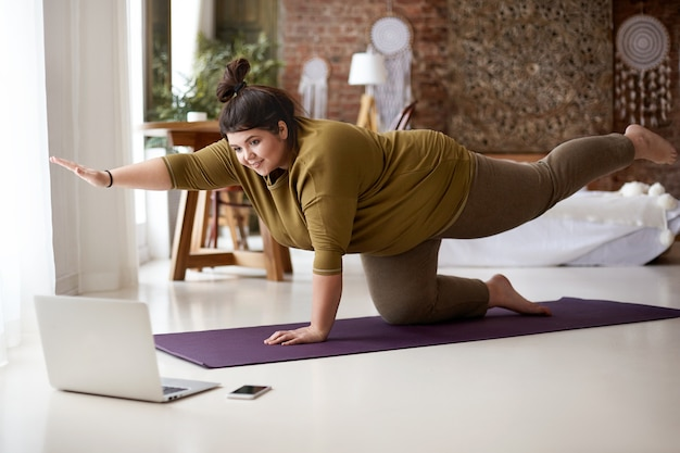 Mujer europea joven gordita obesa con nudo de pelo practicando yoga o pilates en el interior sobre una colchoneta, haciendo ejercicios para fortalecer el núcleo, viendo una lección de video en línea frente a una computadora portátil abierta en el piso