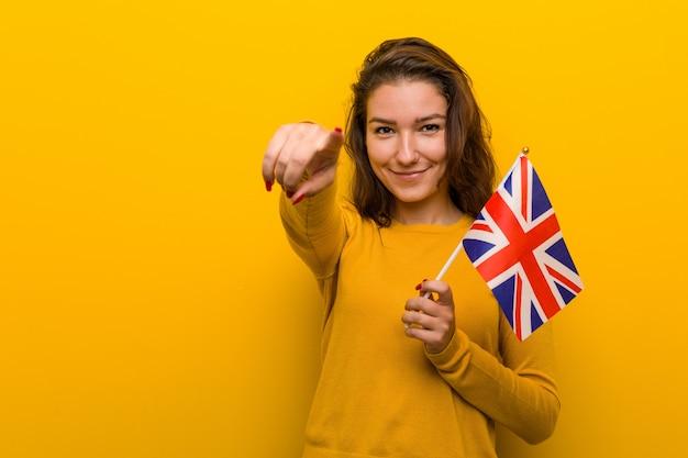 Mujer europea joven que celebra sonrisas alegres de una bandera de reino unido que señala al frente.